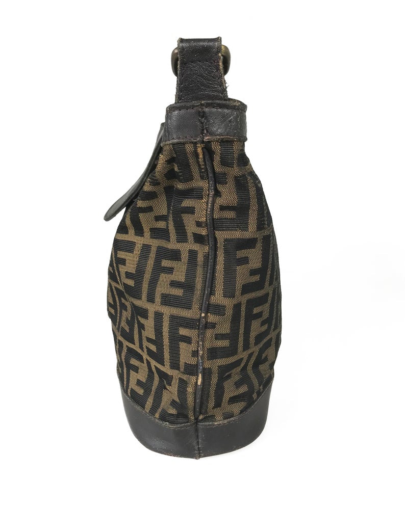 FRUIT Vintage Fendi Zucca cross body bucket bag dating to the 1980s. It features the classic Fendi Zucca monogram canvas, front embossed logo, top push button closure and long adjustable cross body strap..