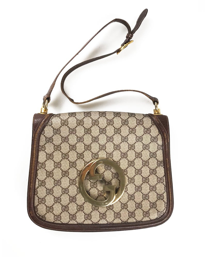 The 1973 Blondie bag is one of the most iconic Gucci styles!  This gorgeous shoulder bag features a very large front double G Gucci Logo at the front, a classic flap closure, brown leather trim and internal zipper pocket.