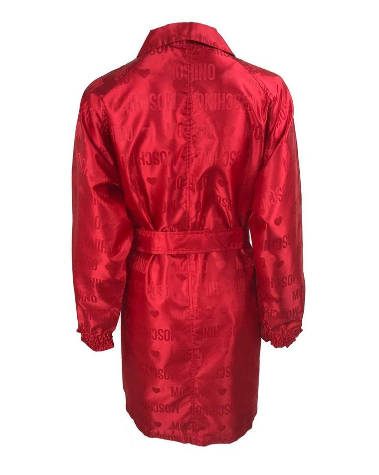 FRUIT Vintage red Moschino Cheap & Chic logo raincoat dating to the 1990s. It features large Moschino logo print all over, heart shaped button closure, front pockets and tie belt.