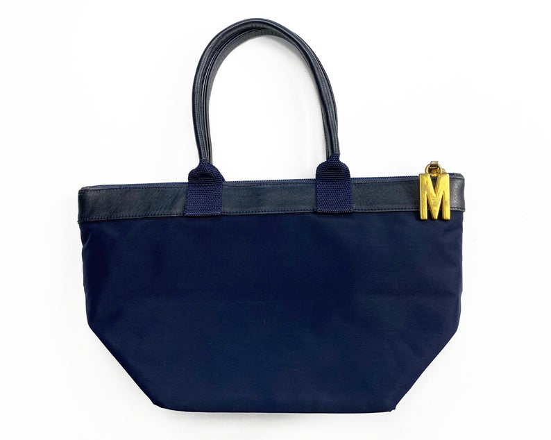 FRUIT Vintage Moschino mini tote bag with the iconic Moschino gold lettering at front. Features a top zipper closure with M logo zipper pull, Moschino logo lining, Moschino Redwall authenticity stamp and logo plaque at side.