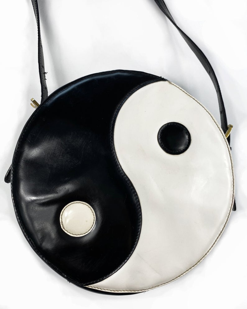 FRUIT Vintage rare Moschino Yin Yang Bag. Dating to the 1990s, the round purse has a large Yin Yang motif on the front made from appliquéd leather.