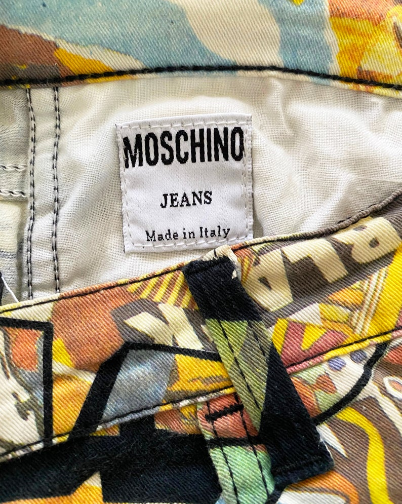FRUIT Vintage Moschino cartoon print jeans dating to the early 1990s. They feature a classic mid-waist cut with a soft stretch denim and the incredible custom 90s Moschino logo print all over