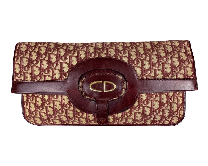 FRUIT vintage 1970s Christian Dior convertible monogram clutch/tote bag as worn by Carrie in Sex and City, it features a Christian Dior 1970s logo at front with snap closure for when it is folded to become a clutch, classic oblique trotter canvas and leather handles.