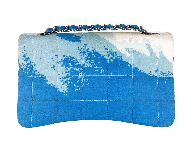 Fruit Vintage Chanel quilted surf print logo canvas flap bag. Features a graphic blue and white surf/wave print on canvas, a square quilted stitching design, classic Chanel flap and zipper closure with Chanel logo pull.
