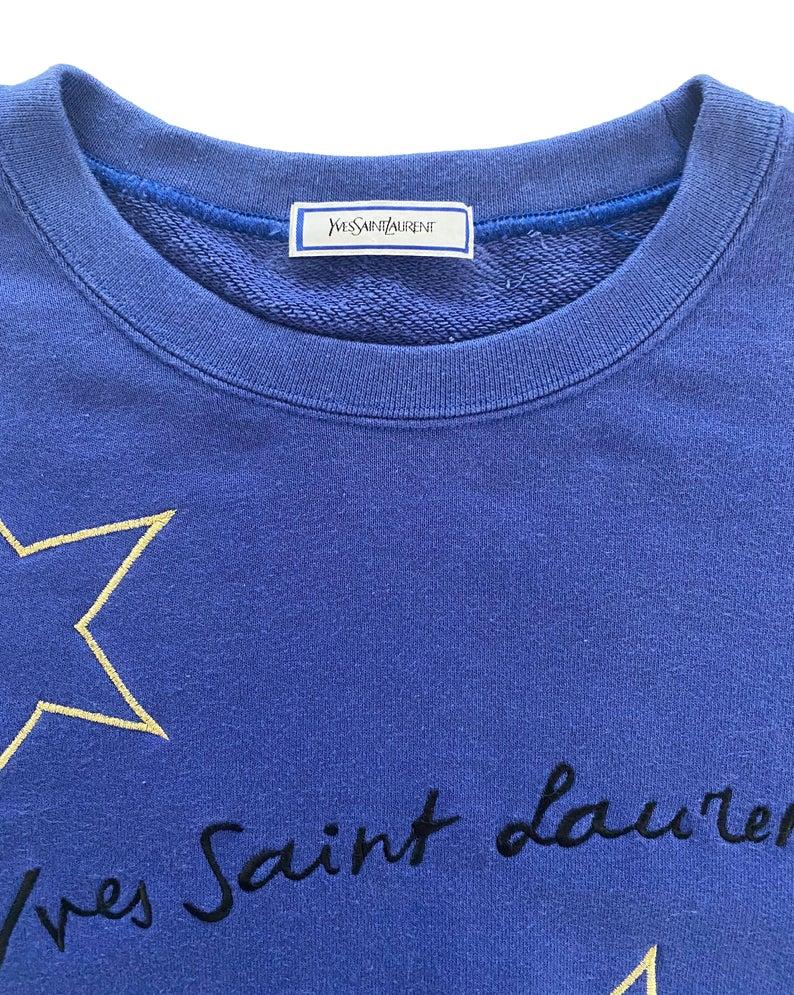 FRUIT Vintage Yves Saint Laurent logo star embroidered blue sweatshirt. Features a large text YSL logo at front and a classic 90's cut.