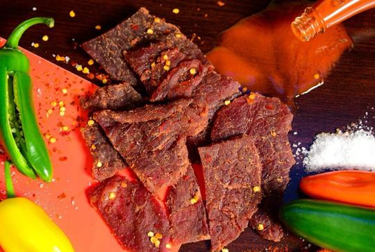 1933 Red Hot Beef Jerky image with ingredients, made in USA original secret jerky recipe, best hot beef jerky, image of cayenne peppers and jerky
