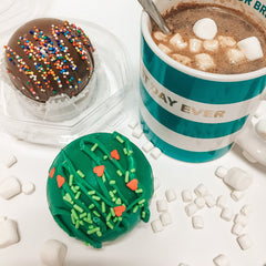 Christmas-themed cocoa bombs and a cup of hot chocolate