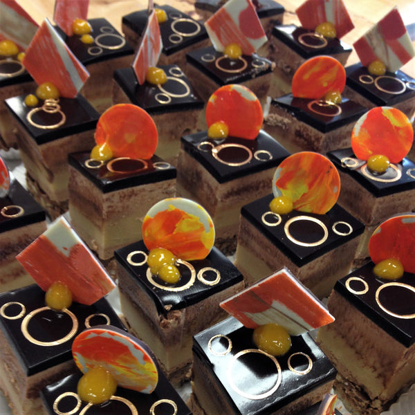Entremet style petits fours with layers of nut-based cakes, chocolate fillings, and chocolate glaze
