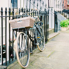 bicycle with basket leaning against fence