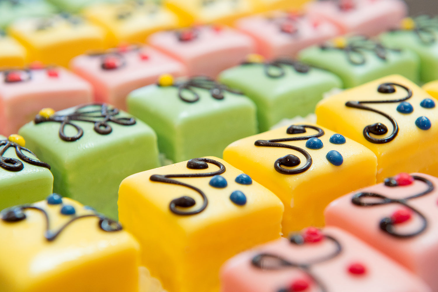 petit fours with pink, yellow, and green hybrid glaze