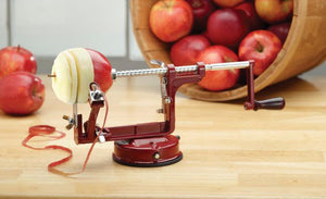 Hand crank apple peeling, coring, and slicing machine from Mrs. Anderson's Baking on table with apples.