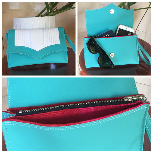 Clutch Bag with mercury pleated turquoise and arctic white vinyl and magenta geometrical lining with inside zipper pocket with two expanding open pockets, magnetic snap closure, and signature Trophy Queen label inside, turns from wrist zipper pull strap into a long strap shoulder bag.