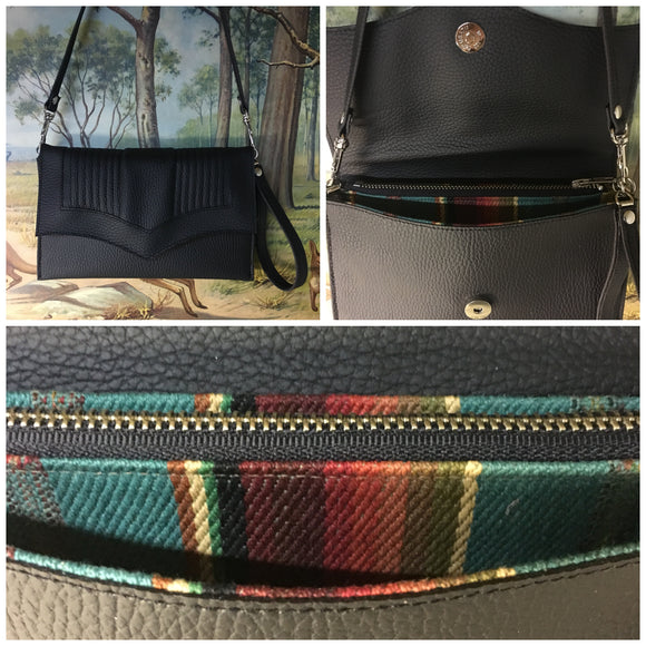 Clutch Bag in mercury pleated pebble blak and turquoise serape lining with inside zipper pocket with two expanding open pockets, magnetic snap closure, and signature Trophy Queen label inside, turns from wrist zipper pull strap into a long strap shoulder bag.