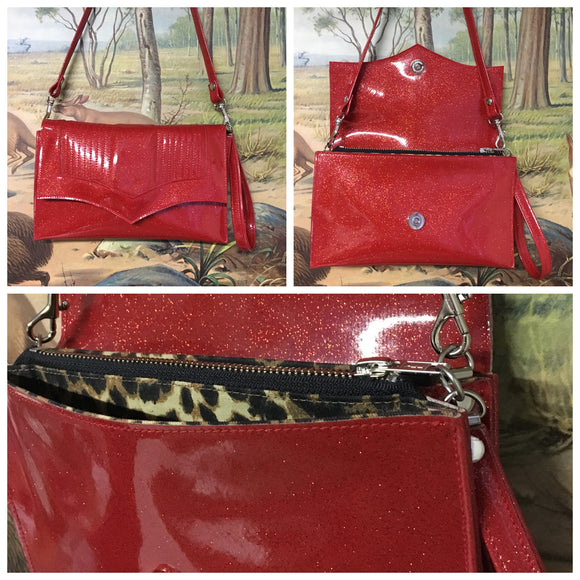 Clutch Bag in mercury pleated cherry red glitter vinyl with leopard print lining with inside zipper pocket with two expanding open pockets, magnetic snap closure, and signature Trophy Queen label inside, turns from wrist zipper pull strap into a long strap shoulder bag.