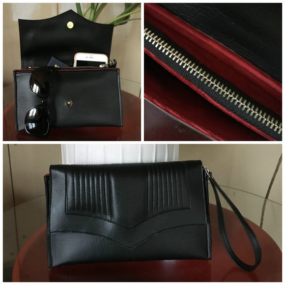 Clutch Bag with mercury pleated black onyx vinyl and sangria red lining with inside zipper pocket with two expanding open pockets, magnetic snap closure, and signature Trophy Queen label inside, turns from wrist zipper pull strap into a long strap shoulder bag.