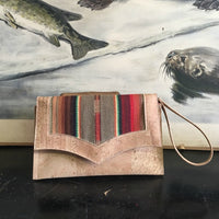 Death Valley Clutch Bag in natural cork featuring light brown serape and sangria red lining with magnetic snap closure, zipper pull as wrist strap, two expanding open pockets and inside zipper pocket. Signature label with serial number included inside.