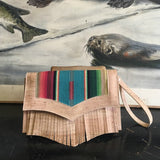 Death Valley Clutch Bag in natural cork plus fringe and featuring turquoise serape and sangria red lining with magnetic snap closure, zipper pull as wrist strap, two expanding open pockets and inside zipper pocket. Signature label with serial number included inside.