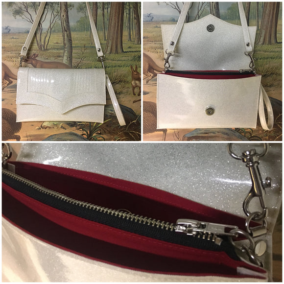 Clutch Bag in mercury pleated white glitter and Ferrari Red lining with inside zipper pocket with two expanding open pockets, magnetic snap closure, and signature Trophy Queen label inside, turns from wrist zipper pull strap into a long strap shoulder bag.