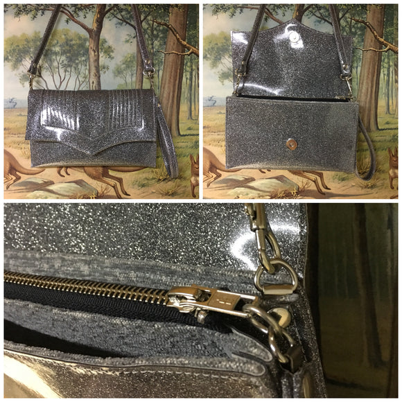 Clutch Bag in mercury pleated steel gray glitter with silver lining with inside zipper pocket with two expanding open pockets, magnetic snap closure, and signature Trophy Queen label inside, turns from wrist zipper pull strap into a long strap shoulder bag.