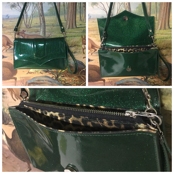 Clutch Bag in mercury pleated green glitter vinyl and leopard print lining with inside zipper pocket with two expanding open pockets, magnetic snap closure, and signature Trophy Queen label inside, turns from wrist zipper pull strap into a long strap shoulder bag.