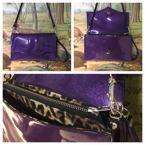 Clutch Bag in mercury pleated purple glitter vinyl and leopard print lining with inside zipper pocket with two expanding open pockets, magnetic snap closure, and signature Trophy Queen label inside, turns from wrist zipper pull strap into a long strap shoulder bag.