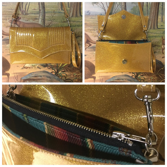 Clutch Bag in mercury pleated gold glitter vinyl and turquoise serape print lining with inside zipper pocket with two expanding open pockets, magnetic snap closure, and signature Trophy Queen label inside, turns from wrist zipper pull strap into a long strap shoulder bag.