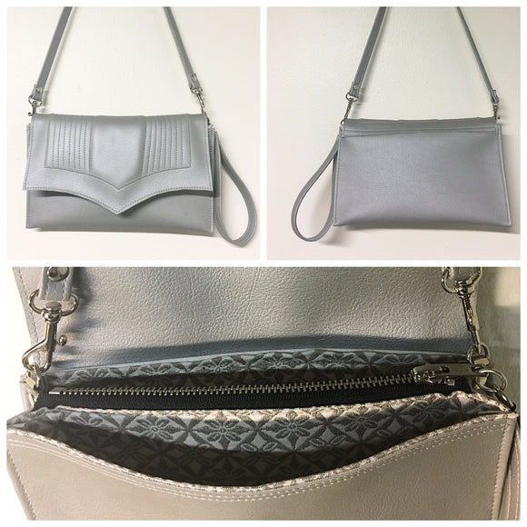 Limited Edition Clutch Bag in silver pebble and snowflake lining with inside zipper pocket with two expanding open pockets, magnetic snap closure, and signature Trophy Queen label inside, turns from wrist zipper pull strap into a long strap shoulder bag.