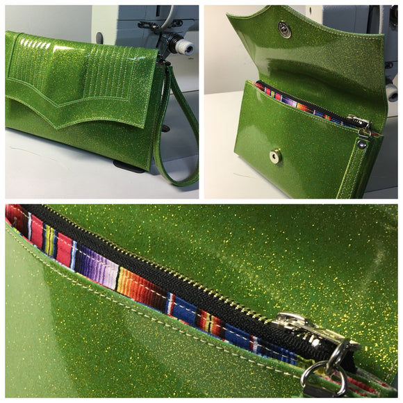 Clutch Bag with mercury pleated lime green glitter vinyl and fiest print lining within inside zipper pocket with two expanding open pockets, magnetic snap closure, and signature Trophy Queen label inside, turns from wrist zipper pull strap into a long strap shoulder bag.