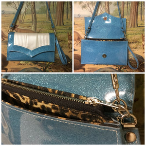 Clutch Bag in mercury pleated sky blue glitter and pearl vinyl with leopard print lining with inside zipper pocket with two expanding open pockets, magnetic snap closure, and signature Trophy Queen label inside, turns from wrist zipper pull strap into a long strap shoulder bag.