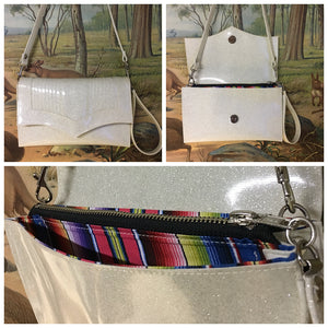 Clutch Bag in mercury pleated white glitter and fiesta print lining with inside zipper pocket with two expanding open pockets, magnetic snap closure, and signature Trophy Queen label inside, turns from wrist zipper pull strap into a long strap shoulder bag.