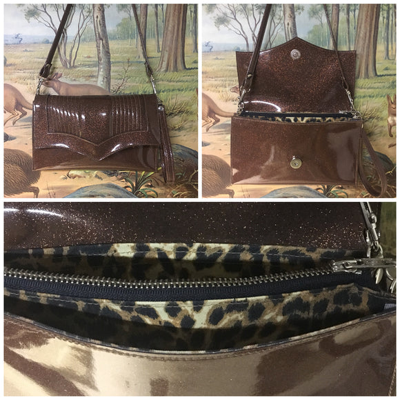 Clutch Bag in mercury pleated root beer brown glitter vinyl and leopard print lining with inside zipper pocket with two expanding open pockets, magnetic snap closure, and signature Trophy Queen label inside, turns from wrist zipper pull strap into a long strap shoulder bag.