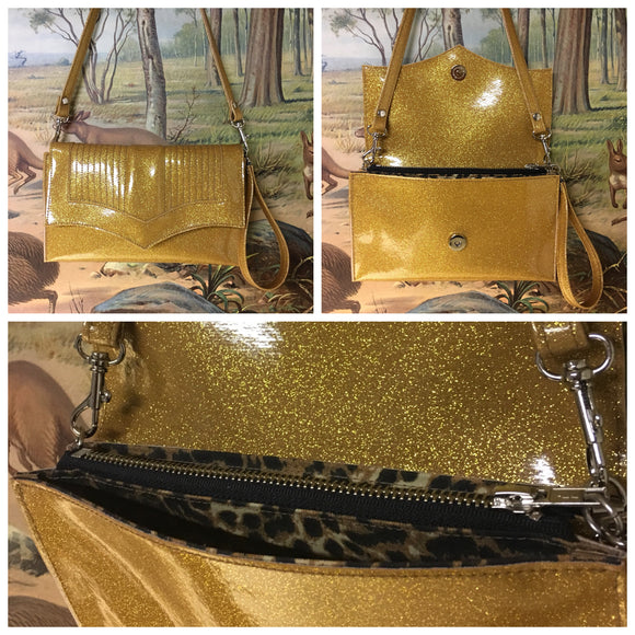 Clutch Bag in mercury pleated gold glitter vinyl and leopard print lining with inside zipper pocket with two expanding open pockets, magnetic snap closure, and signature Trophy Queen label inside, turns from wrist zipper pull strap into a long strap shoulder bag.