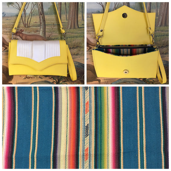 Clutch Bag in mercury pleated lemonade and pearl vinyl with teal serape lining with inside zipper pocket with two expanding open pockets, magnetic snap closure, and signature Trophy Queen label inside, turns from wrist zipper pull strap into a long strap shoulder bag.