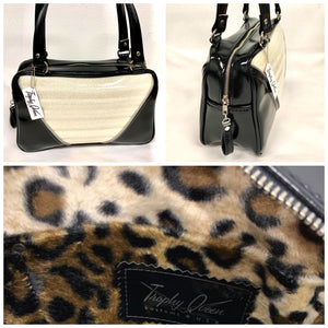 Comet Tote in grease black vinyl and white glitter piping with plush leopard lining handcrafted in California with nickel hardware, an extra set of straps, vinyl zipper pull, inside open divided pocket, zipper pocket with serial number inside and signature Trophy Queen label.
