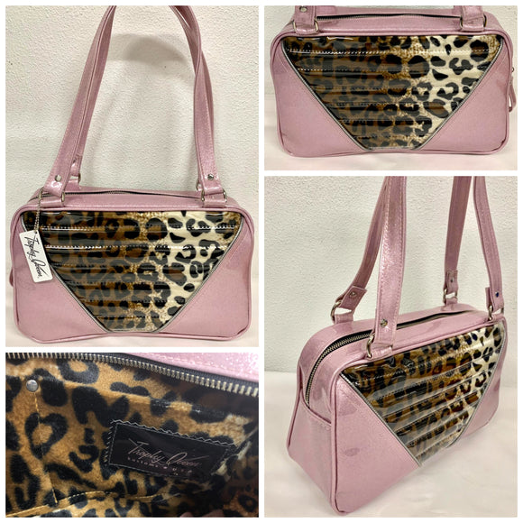Comet Tote in blush pink glitter vinyl and plush leopard with clear overlay with plush leopard lining handcrafted in California with nickel hardware, an extra set of straps, vinyl zipper pull, inside open divided pocket, zipper pocket with serial number inside and signature Trophy Queen label.
