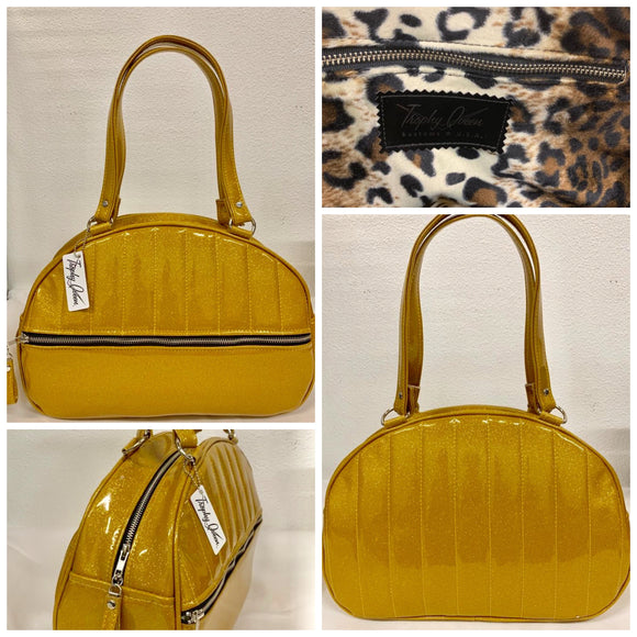 Lucky Strike Bowling Style Bag made with Marigold Glitter Vinyl and lined with Plush Leopard inside with front zipper pocket, shoulder straps with extra set included inside has divided pocket, zipper pocket with hidden serial number inside and signature trophy queen label.