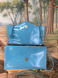 Clutch Bag in sky blue glitter vinyl with pearl white and leopard lining with inside zipper pocket with two expanding open pockets, magnetic snap closure, and signature Trophy Queen label inside, turns from wrist zipper pull strap into a long strap shoulder bag.