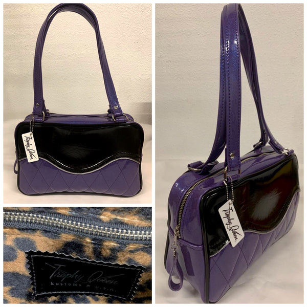 "The Diamond Pleat Tuck and Roll Tote in Beatnik Purple Glitter Vinyl and Grease Black with plush leopard lining is handcrafted in California with nickel hardware and 25"" straps plus it comes with replacement straps. Inside open divided pocket and inside zipper pocket with serial number hidden inside. Nickel feet, vinyl zipper pull, and signature Trophy Queen Label included. The perfect size bag for any trip!"