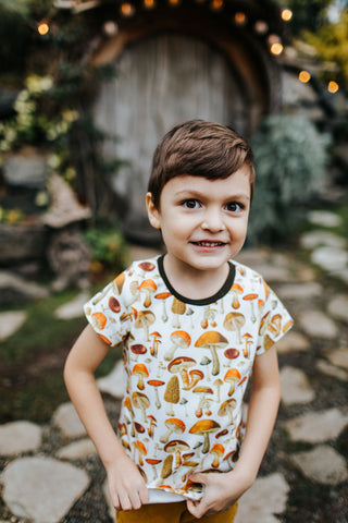 boy wearing a mushroom shirt in front of a hobbit house