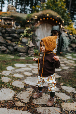 baby boy wearing a bonnet, brown shirt and mushroom pants in front of a hobbit house