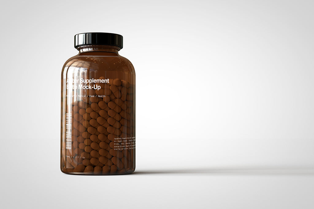 A shiny glass amber supplement/vitamins bottle mock-up full of pills on a white surface with an editable label on the front of the bottle