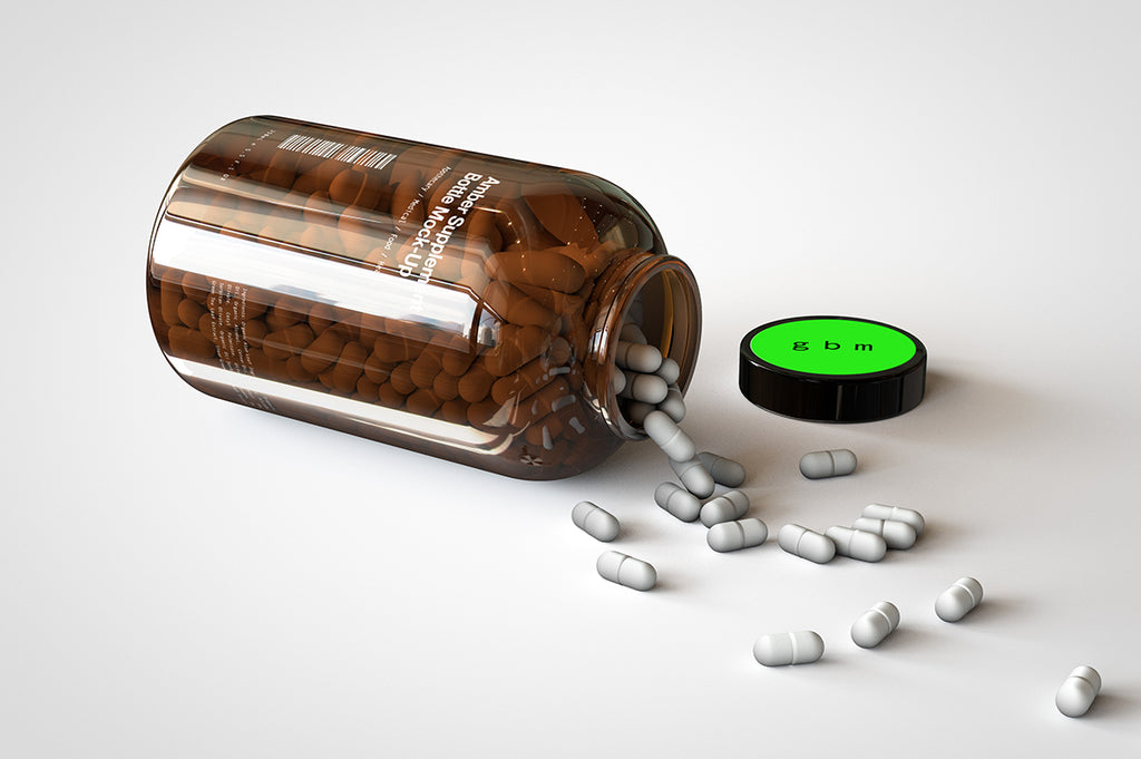 A shiny glass amber supplement/vitamins bottle mock-up full of pills on a white surface with an editable label on the front of the bottle and lid turned on its side with the pills spilling out onto the table