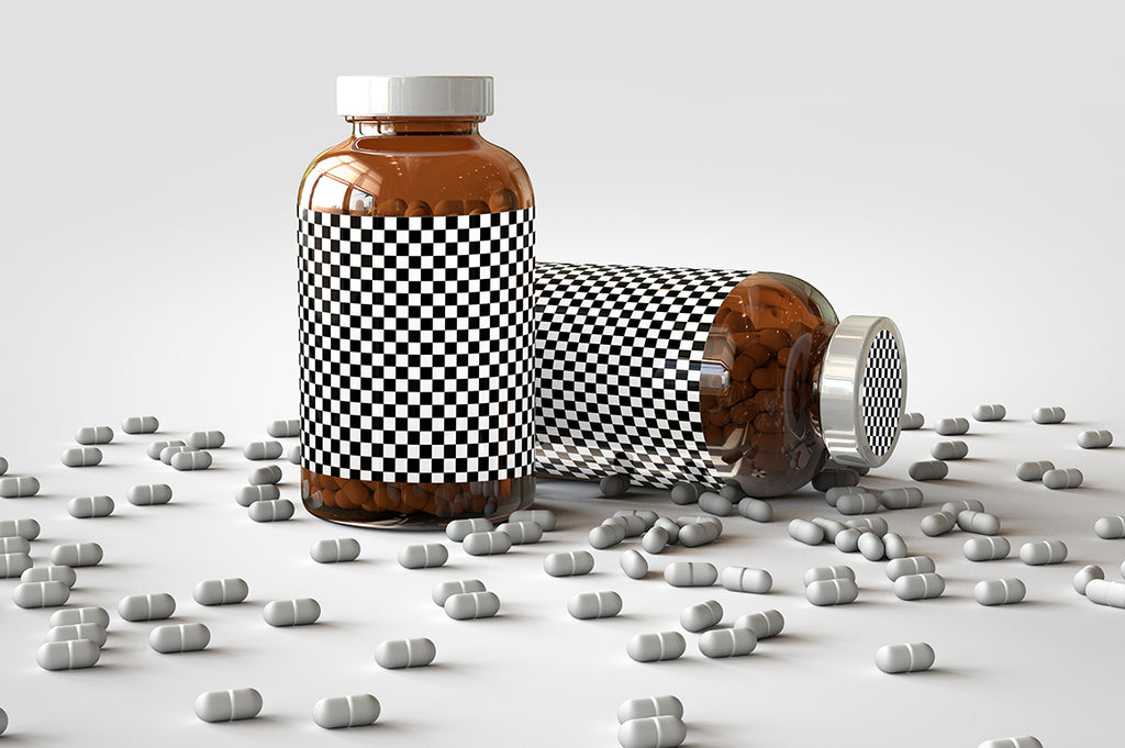 Two shiny glass amber supplement/vitamins bottle mock-up full of pills on a white surface with an editable label on the front of the bottle and lid. One Bottle is standing upright and the other bottle is on its side with the pills scattered out over the table