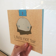 Life's Not Fair book being held