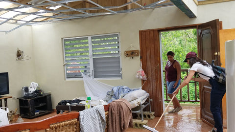 Women helping clean and organize a Huracan Maria victim house photo Around Eco