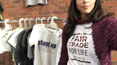 female wearing Fair Trade For Life #ethics ecofriendly top, Around Eco custom made tshirts hanged on a rack at a Brooklyn market