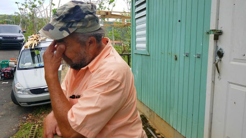 Men crying in front of his house, telling the story about the effect of Huracan Maria photo Around Eco