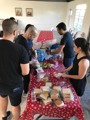 Individuals helping prepare bags of food for the homeless as part of the Around Eco Share the Love program