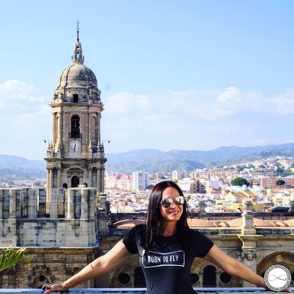 Carmen Dominicci wearing Around Eco travel tshirt with the words Born To Fly