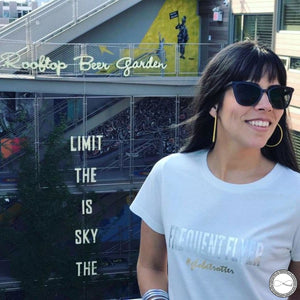 Female Model wearing Around Eco fair trade and ecofriendly white graphic tee with the words Frequent Flyer #globetrotter T-shirt